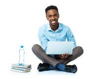Studente di college afroamericano felice che si siede con il computer portatile sul wh Immagini Stock