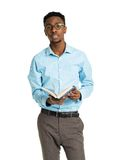 Studente di college afroamericano felice che sta con il libro nel suo Fotografia Stock