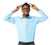 Studente di college afroamericano felice che sta con il libro sul suo Immagini Stock Libere da Diritti