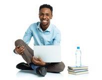Studente di college afroamericano felice con il computer portatile, sittin dei libri Immagine Stock Libera da Diritti