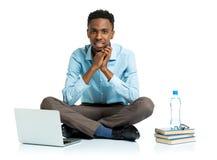 Studente di college afroamericano felice con il computer portatile, sittin dei libri Immagini Stock