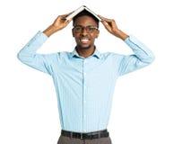 Studente di college afroamericano felice con il libro sul suo sta capo Immagine Stock