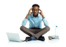 Studente di college afroamericano nello sforzo che si siede con il computer portatile, Fotografie Stock