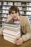 Studente di college annoiato allo scrittorio delle biblioteche Fotografia Stock Libera da Diritti
