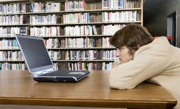 Studente di college annoiato che esamina computer portatile Fotografia Stock