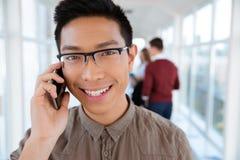 Studente di college asiatico che parla sul telefono Immagini Stock Libere da Diritti