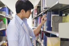 Studente di college asiatico che sceglie un libro in biblioteca fotografia stock libera da diritti