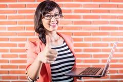 Studente di college asiatico con il computer portatile che mostra pollice Immagine Stock