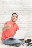 Studente di college bello con il suo computer portatile che dà i pollici su Immagine Stock Libera da Diritti