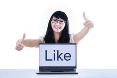 Studente di college che dà i pollici su con come sul computer portatile Immagini Stock