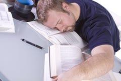 Studente di college che dorme sul suo scrittorio Fotografia Stock
