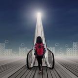 Studente di college che fa un passo verso l'alto sulla scala mobile 1 Fotografie Stock