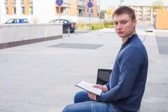 Studente di college che impara sopra il banco con il computer portatile Fotografie Stock Libere da Diritti