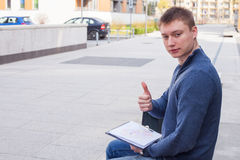 Studente di college che impara sopra il banco con il computer portatile Fotografie Stock