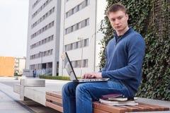 Studente di college che impara sopra il banco con il computer portatile Immagine Stock