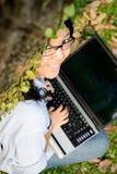 Studente di college che lavora al computer portatile Immagini Stock Libere da Diritti
