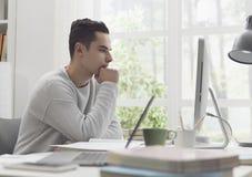Studente di college che per mezzo del computer a casa immagini stock libere da diritti