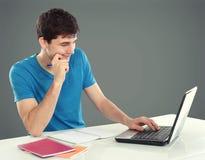 Studente di college che per mezzo del suo computer portatile Immagine Stock