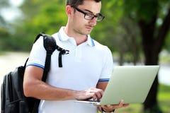 Studente di college che pratica il surfing Internet facendo uso di un computer portatile Fotografie Stock Libere da Diritti