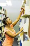 Studente di college che raggiunge libro Fotografia Stock Libera da Diritti