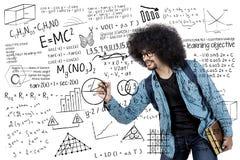Studente di college che scrive formula scientifica Fotografie Stock