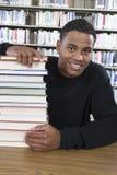 Studente di college che si siede con la pila di libri Fotografie Stock