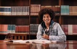 Studente di college che si siede nella biblioteca Immagini Stock