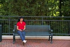 Studente di college che si siede su un banco Fotografia Stock