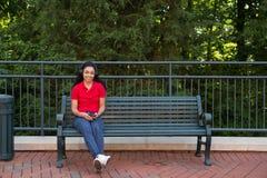 Studente di college che si siede su un banco Immagine Stock Libera da Diritti