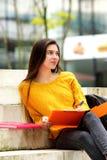 Studente di college che si siede sui punti con il taccuino Immagini Stock