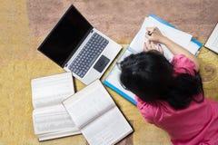 Studente di college che studia sul tappeto Fotografia Stock