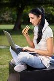 Studente di college che utilizza computer portatile nella sosta che ha pranzo Fotografie Stock Libere da Diritti
