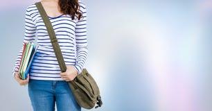 Studente di college con i libri e borsa contro fondo astratto porpora Fotografie Stock