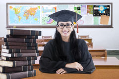 Studente di college con l'abito ed i libri di graduazione Immagine Stock Libera da Diritti