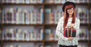 Studente di college con la borsa contro lo scaffale per libri confuso Immagini Stock