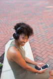 Studente di college con le cuffie e un telefono cellulare Fotografie Stock Libere da Diritti