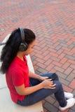 Studente di college con le cuffie ed esaminare un telefono cellulare Fotografia Stock Libera da Diritti