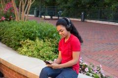 Studente di college con le cuffie ed esaminare un telefono cellulare Fotografia Stock
