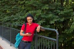 Studente di college con uno zaino che esamina il suo telefono cellulare Fotografia Stock Libera da Diritti