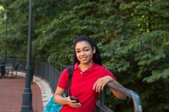 Studente di college con uno zaino che esamina il suo telefono cellulare Immagini Stock Libere da Diritti