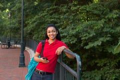 Studente di college con uno zaino che esamina il suo telefono cellulare Immagine Stock
