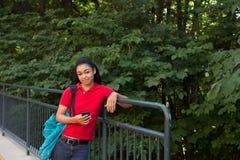 Studente di college con uno zaino che esamina il suo telefono cellulare Fotografie Stock Libere da Diritti