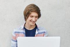 Studente di college d'avanguardia che per mezzo del computer portatile per il suo studio, avendo sorriso piacevole mentre chiacch Fotografia Stock Libera da Diritti