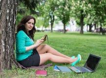 Studente di college della corsa mista che si riposa sul funzionamento dell'erba Immagini Stock Libere da Diritti