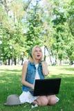 Studente di college della corsa mista che si siede sul funzionamento dell'erba Fotografie Stock Libere da Diritti