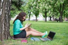 Studente di college della corsa mista che si siede sul funzionamento dell'erba Immagine Stock Libera da Diritti
