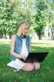 Studente di college della corsa mista che si siede sul funzionamento dell'erba Fotografia Stock Libera da Diritti