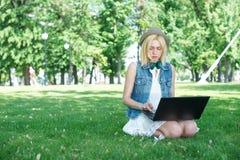 Studente di college della corsa mista che si siede sul funzionamento dell'erba Fotografia Stock