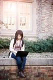 Studente di college della corsa Mixed con il computer portatile fotografia stock libera da diritti