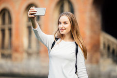 Studente di college della ragazza che si siede fuori della costruzione e che prende un selfie sul fondo della città universitaria fotografie stock